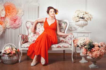 women subtle: Smiling girl sitting on a couch in a red dress, flowers in her hair.
