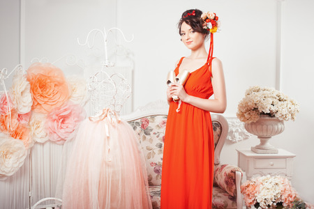 women subtle: Tender girl in the red dress is standing and holding a ballet pointe shoes, hair decorated with flowers. Stock Photo