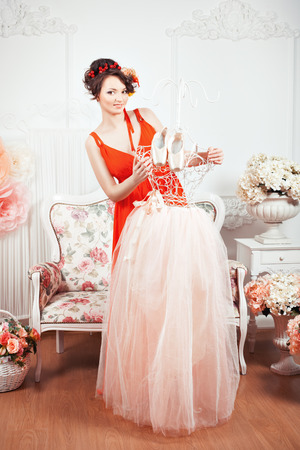 women subtle: Tender girl in a red dress holding a tutu and ballet pointe shoes. Around there are flowers.