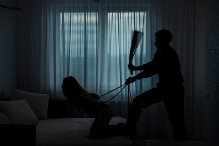 masochism: Black contours silhouette.  Man beats a woman with a whip in a dark room on the bed. Stock Photo
