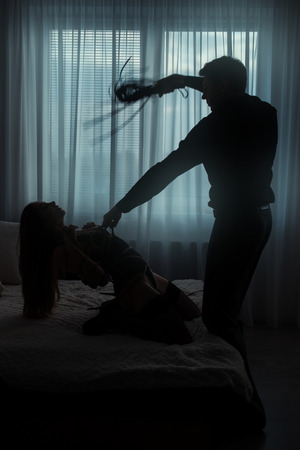 Only visible silhouettes of men and women. Man tyrant bound woman and beat her whip in a dark room.