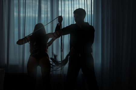 restraints: Only visible silhouettes of men and women. Man beats a woman whip in a dark room. Woman connectivity ropes. Stock Photo