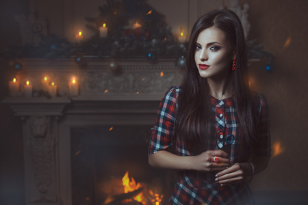 Girl witch with a pair of scissors in his hand standing in front of the fireplace and looks. photo