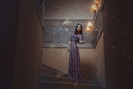 Mystical girl standing on the stairs and conjures. Stock Photo