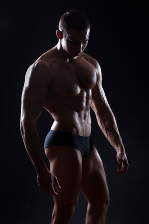 punch press: Beautiful bodybuilder figure in a dark vein underlined muscle. On a black background.