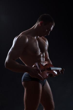 strenuous: Bodybuilder figure in a dark vein underlined muscles. In the hands holding the violin symbol of elegance.