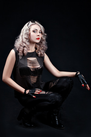 fingerless gloves: Stylish blonde posing in the studio on a black background, in her arms leather fingerless gloves.