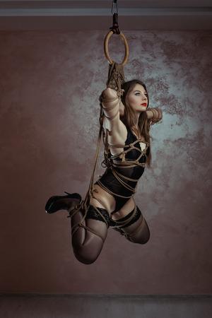 mujeres eroticas: Chica atada con cuerda pesa suspendida. Arte Shibari esclavitud.