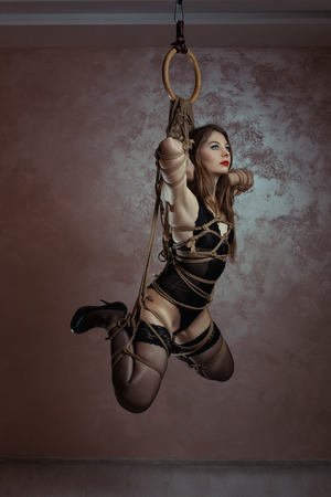 nude women: Girl tied with rope weighs suspended. Art shibari bondage. Stock Photo