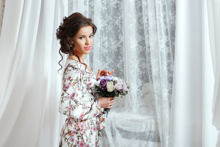loveliness: Lovely girl looks with a smile, holding a bouquet in hands.