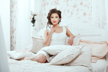 fascination: Cute girl sitting on a white bed among pillows.