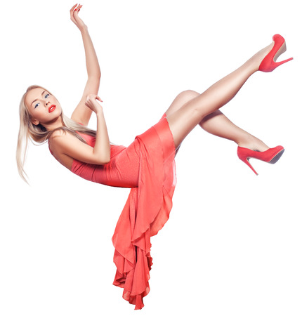 coral colored: Blonde girl hangs in the air and falls. Her coral-colored dress and shoes. Stock Photo