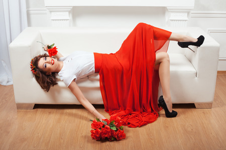minx: Girl in red dress lying on a white sofa and flirting. Stock Photo