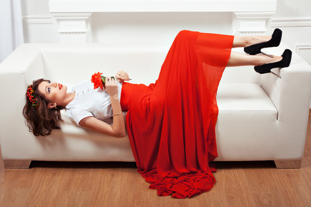 minx: Girl lying on the sofa, her red dress and a flower in her hand. Interior and white sofa.