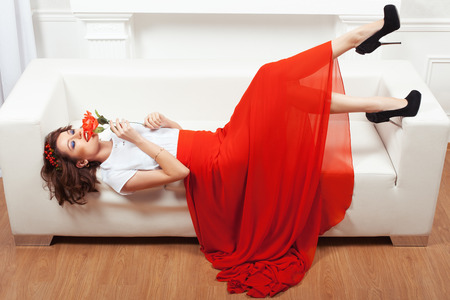 minx: Girl in red dress lying on a white sofa. She put a rose to his lips.