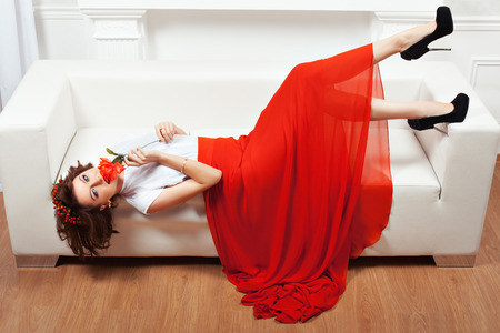 minx: Girl lying on the sofa, her red dress hangs to the floor. She put it to his lips red flower.