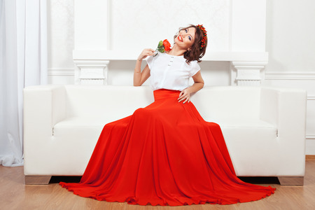 broadly: Beautiful brunette in a red skirt and a wreath sitting on a white couch and smiling broadly.