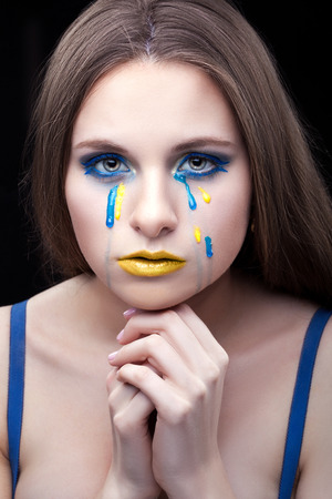 lament: Close-up portrait of a girl with makeup and tears of yellow and blue.