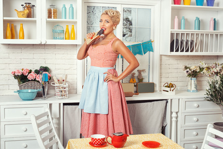 footsie: Woman in the kitchen eating chocolate. She is in a retro style. Stock Photo