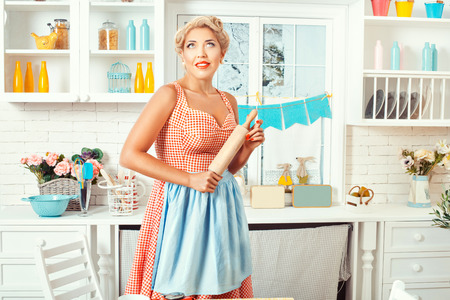 Pin-up style. Girl with a rolling pin stands in the kitchen, look at the ceiling and dreams.