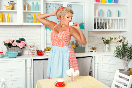 Woman in retro style stands in the kitchen and eating sweet meringue.