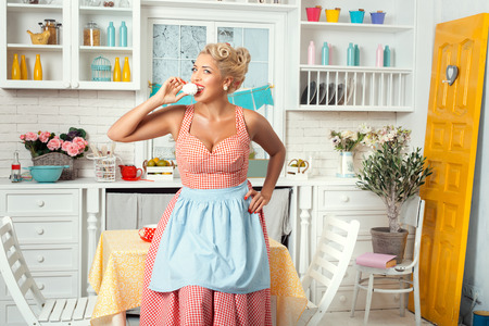 footsie: Smiling woman in kitchen eating sweets. Retro style. Stock Photo