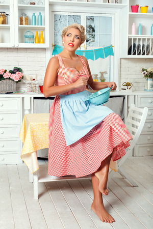 footsie: Woman in the kitchen is going to cook food. She wondered. Retro style. Stock Photo