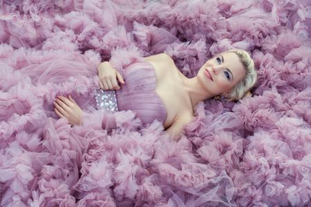 Beautiful young blond girl lying on a lush pink dress. Ball Gown gently pink color.