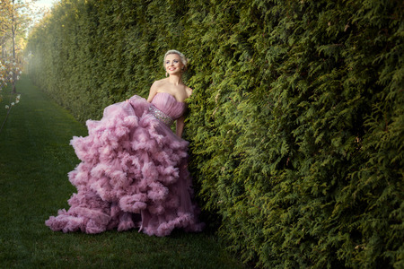 Girl standing in the garden. It magnificent pink dress ball. She smiles. photo
