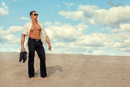 manful: The man in trousers and a white shirt standing in the desert sand. Stock Photo