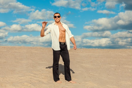 manful: The man with a cigar in his hand stands barefoot on the sand in the desert. He wore a white shirt and trousers.