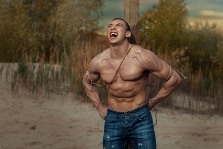 manful: Man with large muscles screaming. He is tied to a pole.