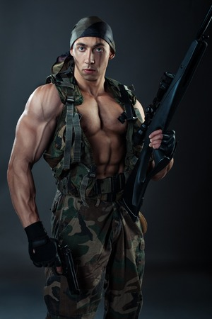 strenuous: Man with large muscles in military uniform with weapon.
