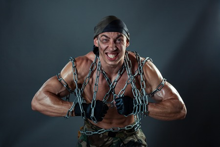 strenuous: A man with huge muscles. He tearing chains that bind his body.