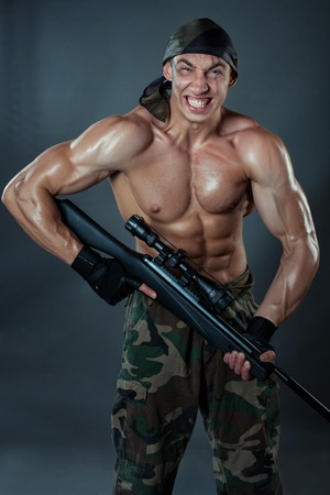 snappy: Military man with huge muscles in the hands holding the rifle. On the optical rifle sniper scope. Stock Photo