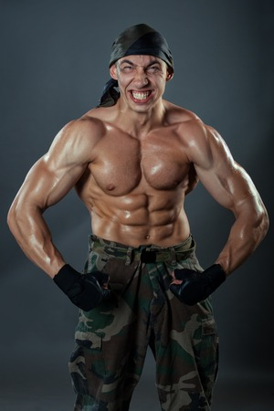 strained: A man in military trousers shows his huge muscles. It is strongly strained muscles and face twisted grimace.