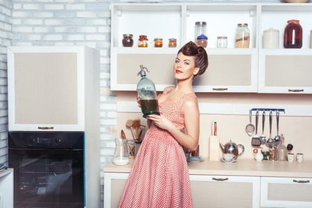 She is the mistress of the kitchen. In her hands she holds a bottle. She smiles.