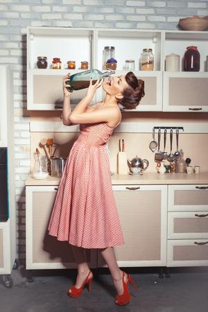 Mädchen in der Küche mit einer Flasche Soda. Sie will aus ihm trinken. Standard-Bild - 41137048
