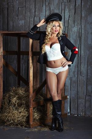 militaire sexy: Brutal femme blonde en lingerie. Sur la t�te d'une arm�e couronner une veste drap�e sur les �paules. Sur les pieds avec des bottes. Prix ??humoristiques sous la forme d'une croix.