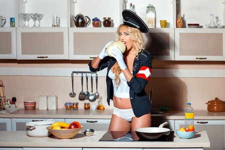 sexiness: Girl in the kitchen eat cabbage. It is for humor dressed in uniform cap and jacket. Humorous awards in the form of a cross.