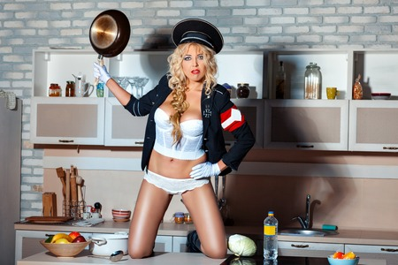 sexiness: Brutal girl standing on a table in the kitchen. In her hand she holds a pan. She is wearing a military uniform humorous.