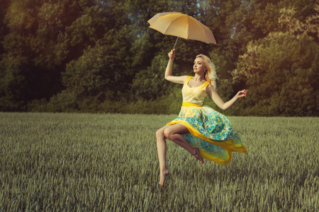 poise: Girl levitates over the green field on the umbrella. She is wearing a nice summer dress. Stock Photo