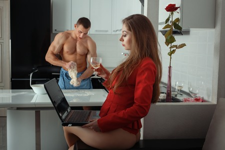 skivvy: Foreground girl behind a laptop. She drinks wine. The man is out of focus cook. They are in the kitchen.