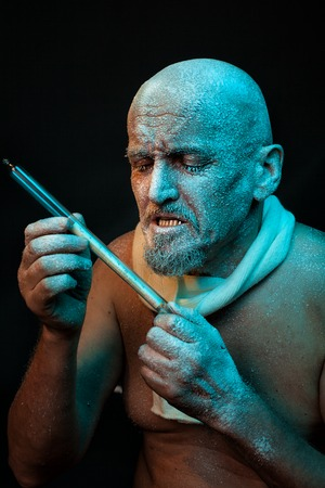 frenetic: The bald man looks at the thermometer. He has a mustache and beard. His head was frozen and covered with frost. Stock Photo