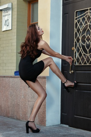 Girl suffers from trying to open the door. She put her foot in the door, her hands pulling the handle. Stock Photo