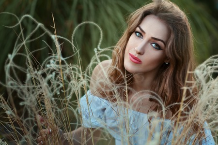 Portrait of a beautiful girl in dry grass close-up.