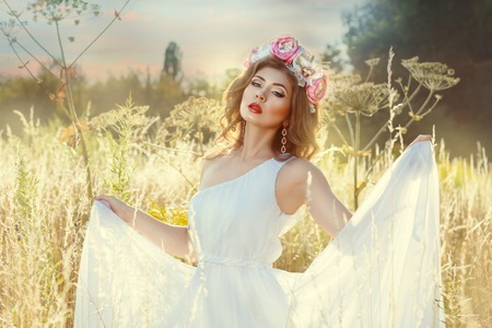 catchy: The beautiful gentle girl in white dress. She stands in a field in the grass. Stock Photo