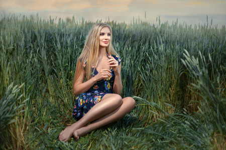 grain fields: Beautiful young blond woman sitting in a field of wheat. In her hands she holds the spike.