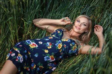 Blond Girl lying in the grass and smiling. Girl has blue eyes.