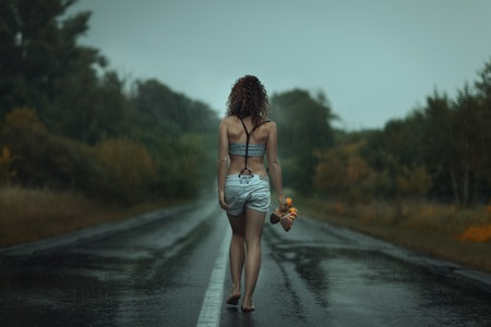 Girl back. Walks on the road. Under rain. She is barefoot.